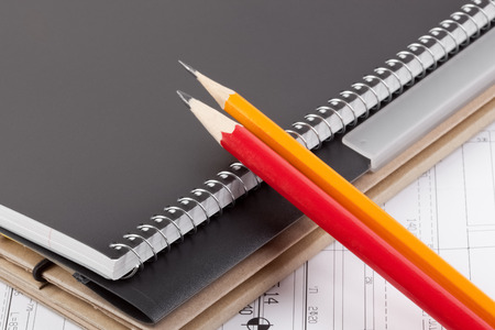 diagonal diary education: Notebook, folder and pencils on top of architectural drawings.