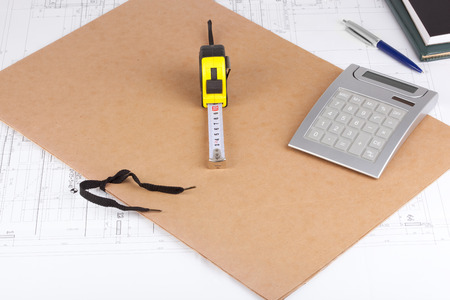 Measurement tools and a folder on top of architectural drawings. photo