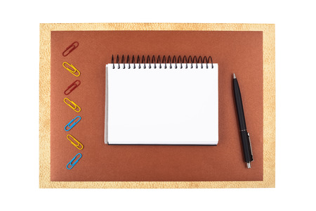 Office accessories on brown textured paper: colored paper clips, a black ballpoint pen, sheets of textured paper and a notebook. Composition isolated on white background. photo