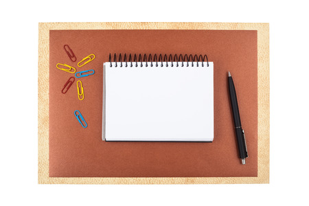 roster: Office accessories on brown textured paper: colored paper clips, a black ballpoint pen, sheets of textured paper and a notebook. Composition isolated on white background.