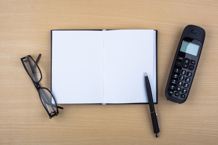 An open notebook, a ballpoint pen, eyeglasses and a black phone on wooden texture imitating an office desk. photo