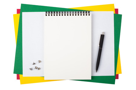 formalization: A notebook, push pins and a black ballpoint pen on sheets of colored paper.  Composition isolated on white background.