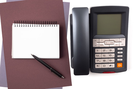 A notebook on sheets of textured colored paper, a black ballpoint pen and a digital phone isolated on white background. photo