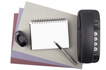 roster: A notebook, a fountain pen, an ink bottle and a black phone on sheets of textured colored paper isolated on white background.