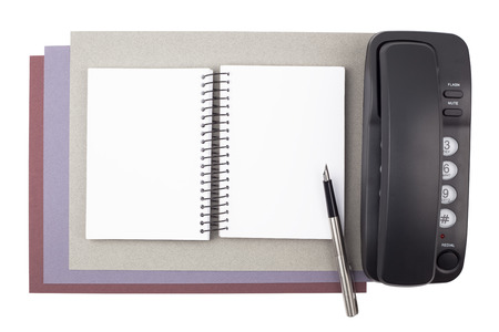 A notebook, a fountain pen, and a black phone on sheets of textured colored paper isolated on white background. photo