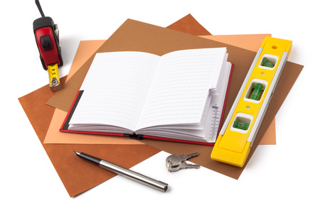 A notebook, a fountain pen, a tape measure, keys and a yellow level on sheets of textured colored paper. photo
