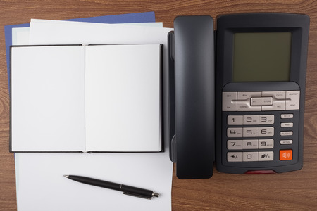 formalization: An open notebook, a ballpoint pen and a digital phone on wooden texture imitating a office desk. Stock Photo