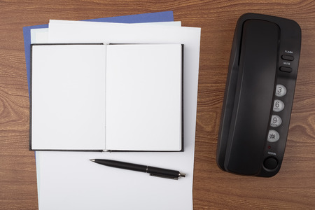 formalization: An open notebook, a ballpoint pen and a black phone on wooden texture imitating a office desk.