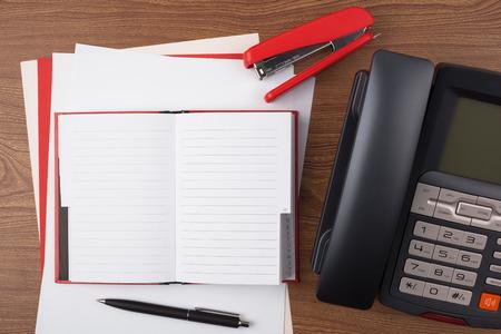 office stapler: An open notebook, a stapler a ballpoint pen and a digital phone on wooden texture imitating a office desk. Stock Photo