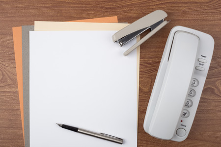 Sheets of paper, a stapler, a fountain pen and a white phone on wooden texture imitating a office desk.