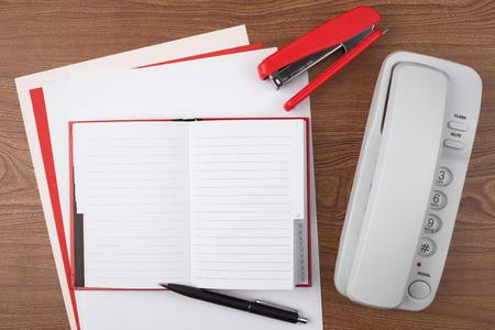 An open notebook, a stapler a ballpoint pen and a white phone on wooden texture imitating a office desk. photo