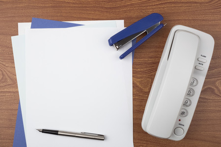 Sheets of paper, a stapler, a fountain pen and a white phone on wooden texture imitating a office desk. Stock Photo