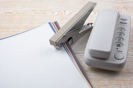 Sheets of paper, a white phone and a stapler symbolizing paper binding on wooden texture imitating a desk.