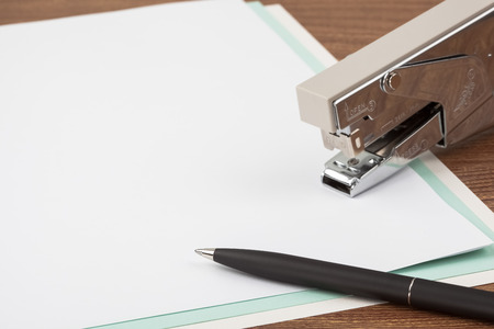 missive: Sheets of paper, a stapler and a black ballpoint pen on wooden texture imitating a desk. Stock Photo