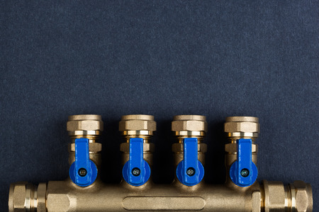 Brass manifold, PEX Fittings with ball valves on textured dark background.