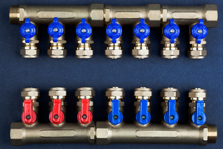 Brass manifold, PEX Fittings with ball valves on textured dark background. Foto de archivo