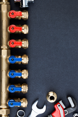 Brass manifold valve and wrenches on textured dark background.