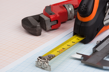 Wrench, caliper and tape measure on top of blue graph paper.