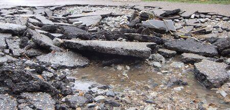 Road of the water erosion, broken asphalt background. Danger hole, stone gray backdrop. Close-up photo. Banco de Imagens