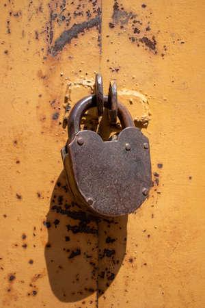 Old rusty padlock on metal yellow door. Stock fotó - 154774689