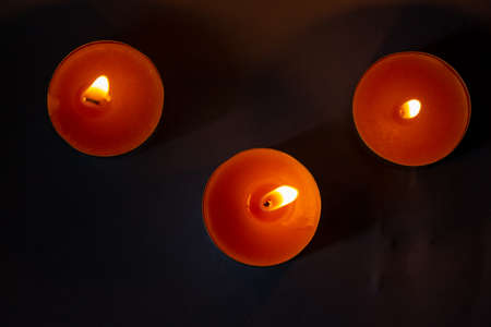 Composition of three candles on dark luxury night background. Black table, top view. Candles Burning at Night. Orange taper burning in focus, foreground. illustration design. Photo.