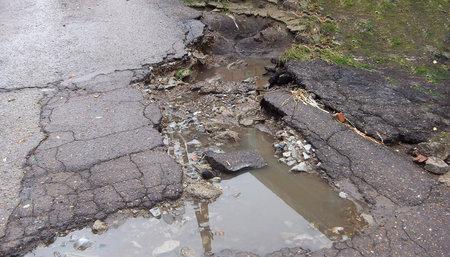 Broken asphalt, road, water erosion, background. Danger hole, stone gray backdrop. Close-up photo.