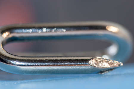 Art background, single metal nail with a bend out of focus. Perfectly bokeh effect, macro. Blur detail of object.