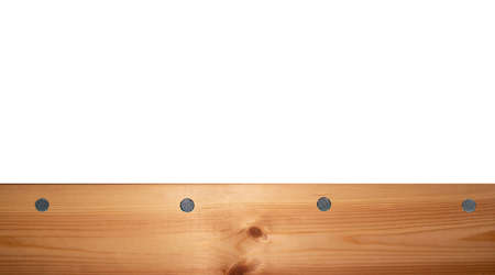 Top view light wood texture surface with natural pattern and metal nail heads or hats. Wooden pine board isolated on white. Spruce table with knots. Timber backdrop. Rustic craft. Workbench. Box edge. 免版税图像