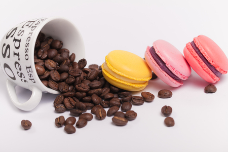 Cup with coffee beans with colorful delicious French macaroons on white background close up