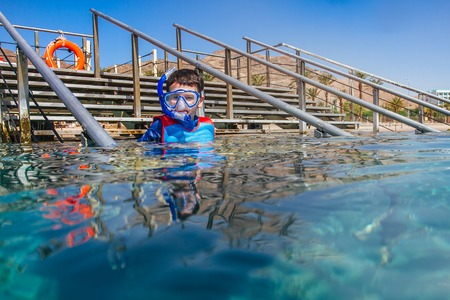 kid before Snorkeler diving along the brain coral