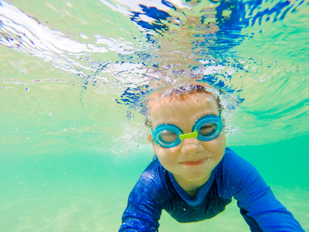 swimm: Underwater Young Boy Fun in the sea with Goggles. Summer Vacation Fun.