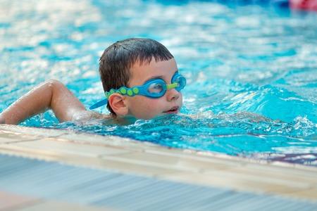 Sluit omhoog van jonge jongen die in pool zwemt. Stockfoto