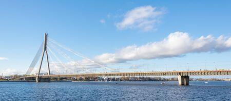 ?able Brücke über den Fluss Daugava in Lettland am blauen Himmel und weißen Wolken Hintergrund. Kabelbrücke über den Fluss.