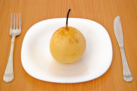 single pear on white plate with fork and knife photo