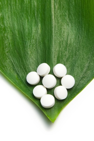 white pills on a green leaf, natural medicine concept Stock Photo - 8631498
