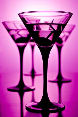 four glasses of martini on purple background, shallow depth of field