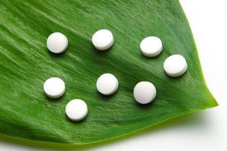 white pills on a green leaf, natural medicine concept Banco de Imagens