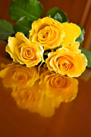 three yellow roses on brown table Stock Photo - 8885056
