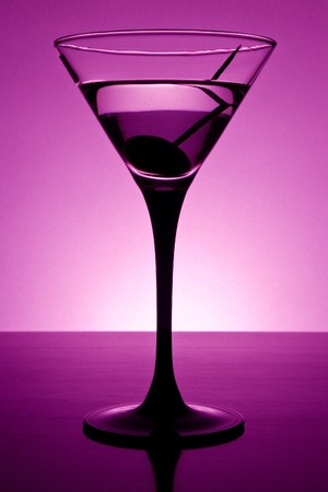 Martini glass on table in purple light photo