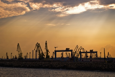 silhouette of cranes in shipyard at dusk photo