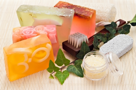 four handmade soaps with loofah brush and sea-salt on bamboo board photo