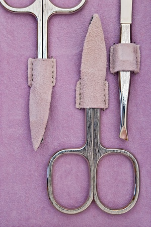 manicure scissors and pincer on purple leather photo