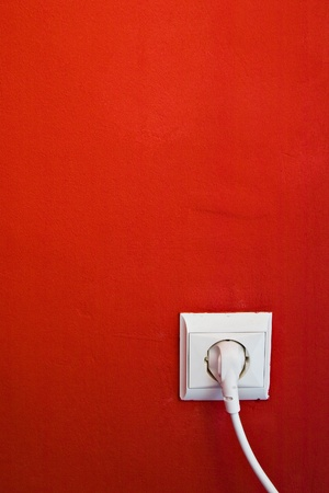 electric consumption - electric outlet on red wall photo