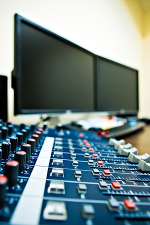 music production: audio mixer with computer in background - shallow depth of field