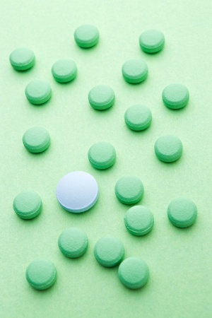 green pills and one blue pill on green background photo