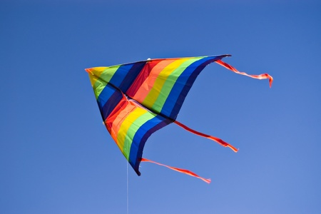 flying a kite: colorful kite on blue sky