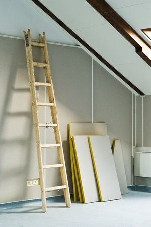 wood step ladder and construction materials in attic room photo