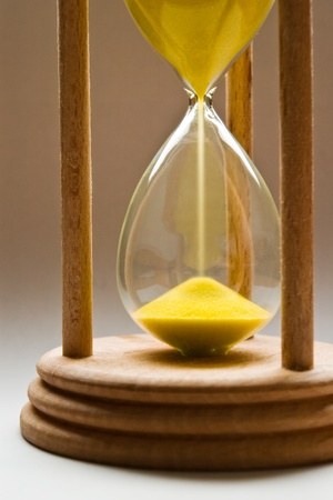 sand timer: hourglass with yellow sand and shallow depth of field