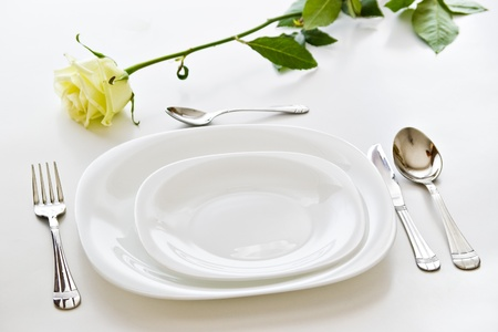 place setting with white plates and beige  rose flower photo