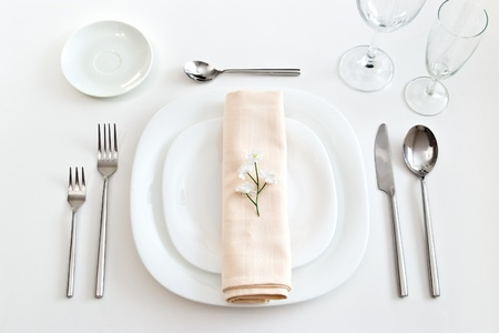 place setting with white plates forks glasses beige napkin and little flower Stock Photo - 9786891